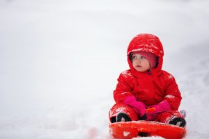 Child on sledge in snow